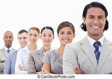 Big close-up of happy colleagues crossing their arms in a single line looking straight with focus on the first woman