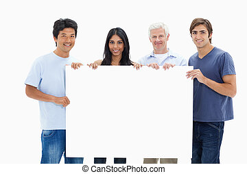 People in jeans holding a big sign against white background