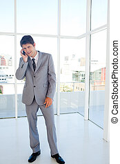 Smiling businessman making a call while leaning his head to the