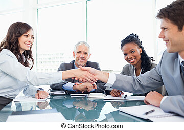 Young smiling executives shaking hands in front of their...
