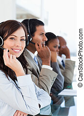 Young smiling call centre agent looking at the camera while...