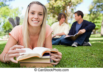 Smiling girl lying in front of her books in a park