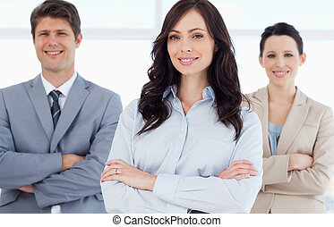 Young smiling executive woman crossing her arms in front of co-workers