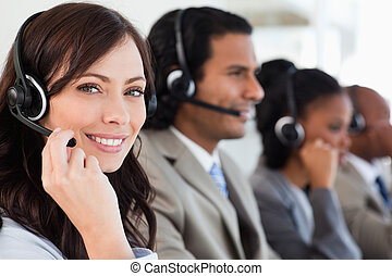 Smiling worker doing her job with a headset while looking at...