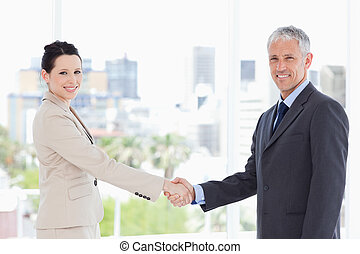 Two business people shaking hands while smiling and looking...