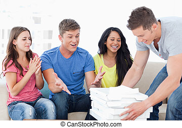 Friends celebrating as one guy brings pizza to them - A...