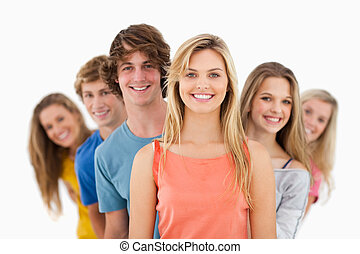 Group standing behind one another at varied angles - A...