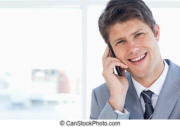 Young businessman laughing while talking on the phone
