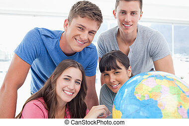 A group of people smiling as they all look into the camera with a globe next to them