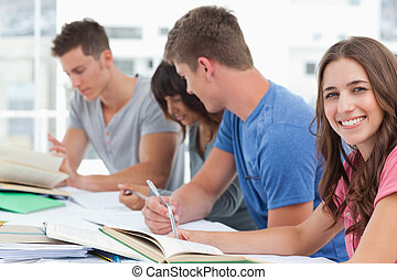 A side view shot of people studying hard as one woman looks into the camera and smiles