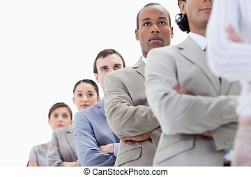Low-angle shot of a serious business team crossing their arms in a single line with focus on the second man
