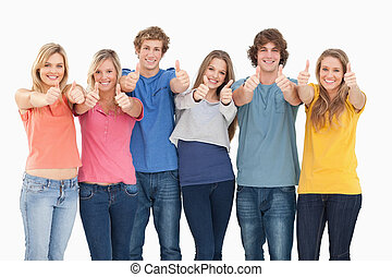 Six friends giving thumbs up as they smile - Six friends...