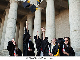 Happy graduates throwing their hats in the sky in front of...