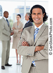 Young businessman standing upright while crossing his arms