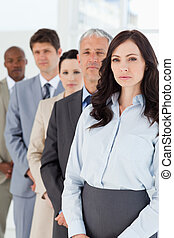 Young serious executive woman standing upright in front of...