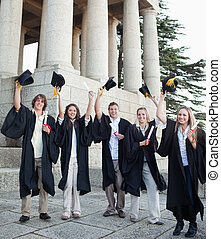 Five happy grad students raising their hats