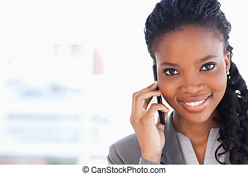 Young smiling businesswoman looking ahead while talking on a...