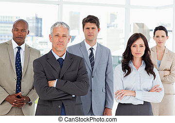 Business team seriously looking at the camera while standing in front of a window