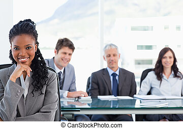 Confident smiling executive sitting in a meeting room while...