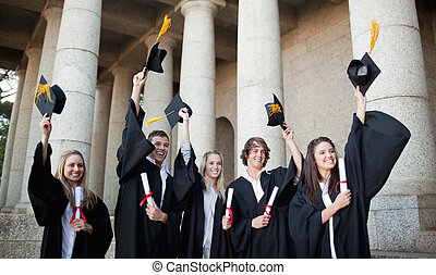Smiling graduates holding up their hats in front of the...