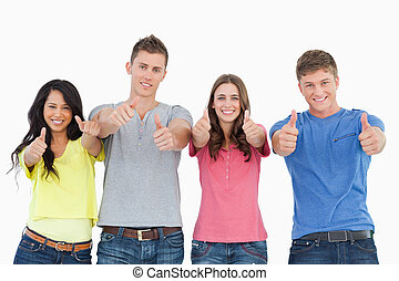 Four people standing beside each other give thumbs up - A...