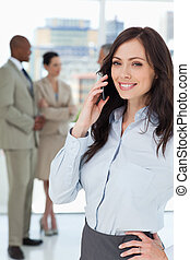 Smiling executive woman talking on the mobile phone with one hand on her hip