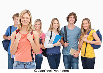 A smiling girl stands in front of her college friends as...