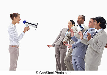 Woman yelling at business people through a megaphone against...