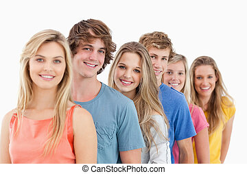 A smiling group standing behind each other at an angle while...