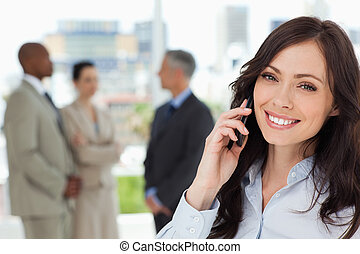 Young smiling executive woman on the cell phone and tilting...