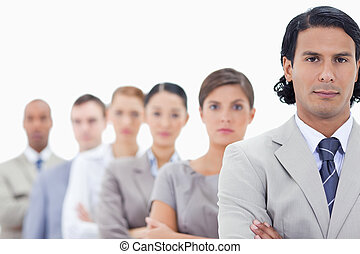 Big close-up of a serious business team crossing their arms in a single line looking straight with focus on the first man