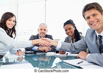 Young smiling executives shaking hands while looking at the...