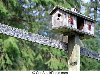 Double birdhouse - A double birdhouse on top of a post with...