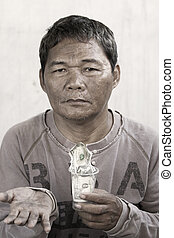 Beggar - A homeless man holding a cup with money