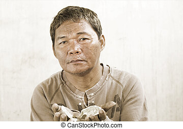 old asian beggar man with money in his dirty hand.