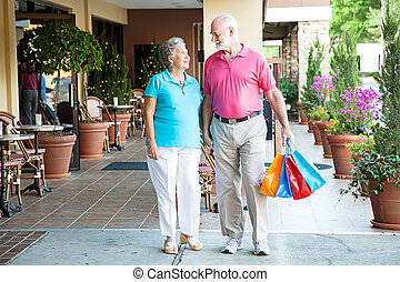 Shopping Hand-in-Hand - Senior couple shopping together at...