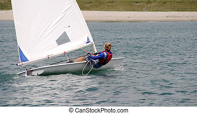 Sailing - Young sailor in a small boat sailing on the lake