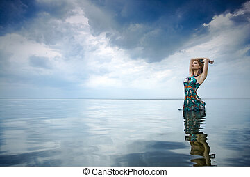 The girl in a summer dress in water