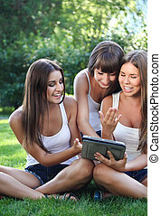 Happy young girls with a tablet computer