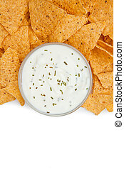 Close up of a bowl of dip with herbs surrounded by nachos...
