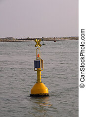 Yellow signalling buoy in the middle of the sea to help...