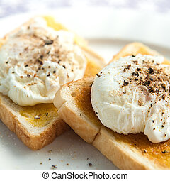 Two delicious poached egg on toast with freshly cracked...