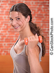 Brunette woman lifting weights