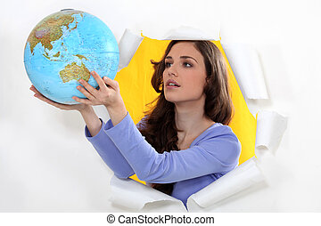 Woman getting out of hole with globe