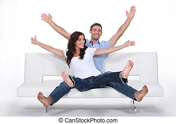 Excited couple sat on sofa with arms in the air