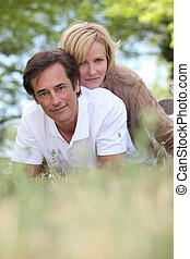 Married couple laying in a field