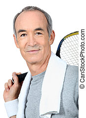 A mature man playing tennis.