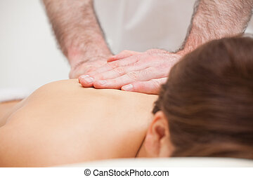 Close-up of a doctor massaging the back of a woman