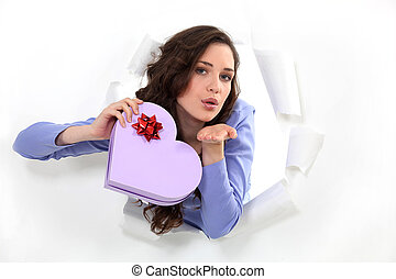 brunette holds box in shape of heart blowing a kiss