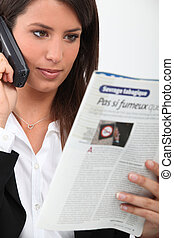 Young woman on telephone reading French magazine